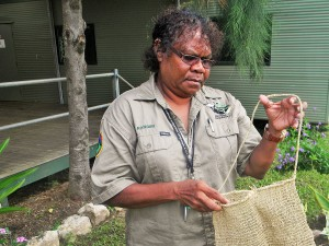 Cultural Heritage Officer, Jennifer Creek holding a grass weaved dillybag
